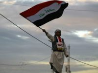 An Iraqi man waves his national flag in Baghdad's Tahrir Square on December 10, 2017, during a gathering celebrating the end of the three-year war against the Islamic State (IS) group