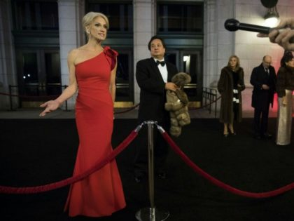 George Conway stands in the background as his wife Kellyanne Conway speaks to reporters at an event for President Donald Trump's 2017 inauguration