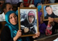 Families of victims of Tunisia's 2011 revolt against dictatorship carry portraits of their loved ones during a trial in Kasserine on July 13, 2018