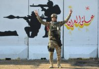 A member of Iraq's Rapid Response military unit poses in front of a mural glorifying Iraqi forces
