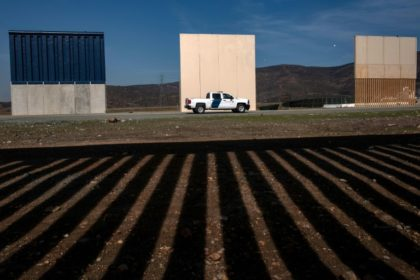 Customs and Border Protection agents drive by prototypes of a US border wall as seen from behind the Mexico-US border fence in Tijuana, Mexico
