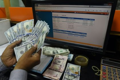 A Pakistani dealer counts US dollars at a currency exchange shop in Karachi on November 30, 2018