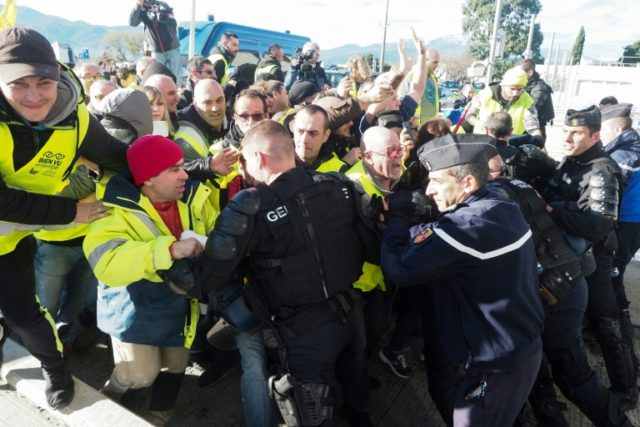 "Police officers repel ""yellow vest"" protesters as they demonstrate against the rising cost of living at the A9 highway toll at Le Boulou, southern France"