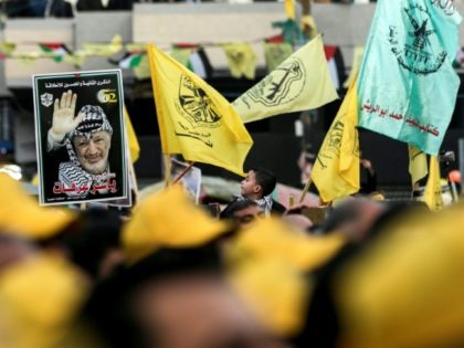 Fatah supporters hold up a portrait of late Palestinian leader Yasser Arafat during a rally in Gaza City on December 31, 2017