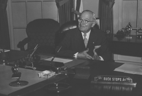Former President Harry Truman sitting at the desk in a reproduction of the president's office in the Harry S. Truman Library. The buck Stops Here sign is on the desk.