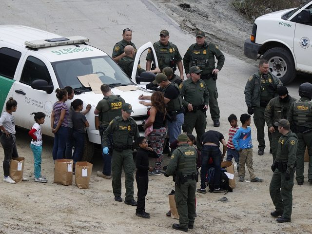 U.S. Border Patrol agents process a group of Honduran asylum seekers consisting almost entirely of women and children, after they crossed the U.S. border wall into San Diego, California from Tijuana, Mexico, Monday, Dec. 10, 2018. (AP Photo/Rebecca Blackwell)