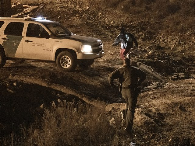 A border patrol officer fails to arrest a migrant running after jumping the United States border fence to San Diego, from Tijuana, Mexico, Tuesday, Dec. 25, 2018. Discouraged by the long wait to apply for asylum through official ports of entry, many Central American migrants from recent caravans are choosing …