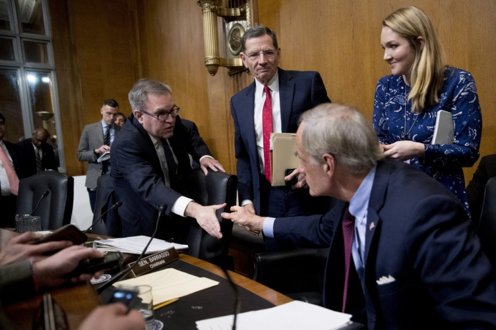 Chairman John Barrasso, center, watches as Andrew Wheeler, left, shakes hands with Ranking Member Thomas Carper, second from right, as he departs after testifying at a Senate Environment Committee hearing on January 16, 2019. (Andrew Harnik/AP Photo)