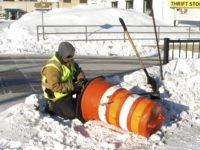 Jason Gion, an employee for the city of Fargo, N.D., works in 15-below temperatures while repairing a warning cone meant to prevent drivers from running into a sidewalk barrier at a road construction project near the city's downtown on Friday, Jan. 25, 2019. The warning cone was damaged after a …