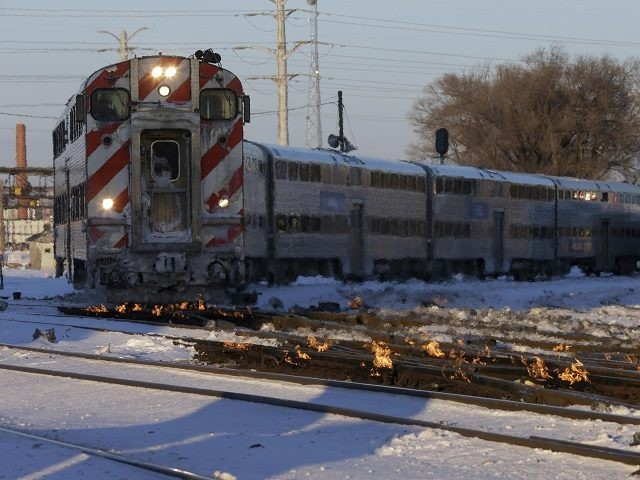 A Metra train moves southbound to downtown Chicago as the gas-fired switch heater on the rails keeps the ice and snow off the switches near Metra Western Avenue station in Chicago, Tuesday, Jan. 29, 2019. Forecasters warn that the freezing weather Tuesday will get worse and could be life-threatening. (AP …
