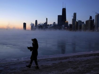 A person walks along the lakeshore, Wednesday, Jan. 30, 2019, in Chicago. A deadly arctic deep freeze enveloped the Midwest with record-breaking temperatures on Wednesday, triggering widespread closures of schools and businesses, and prompting the U.S. Postal Service to take the rare step of suspending mail delivery to a wide …