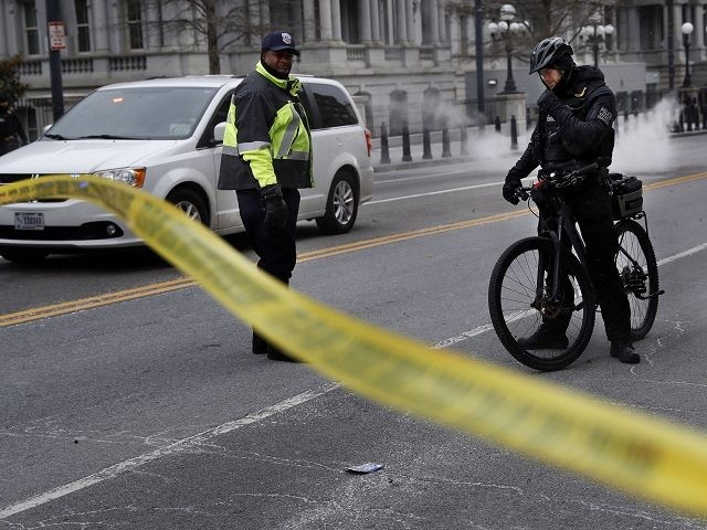 With steam from an underground grate in the background, a Metropolitan Police officer and Secret Service Police officer react to a large gust of frigid wind while blocking the road on 17th Street at the intersection with Pennsylvania Avenue near the White House in Washington, Wednesday, Jan. 30, 2019. (AP …