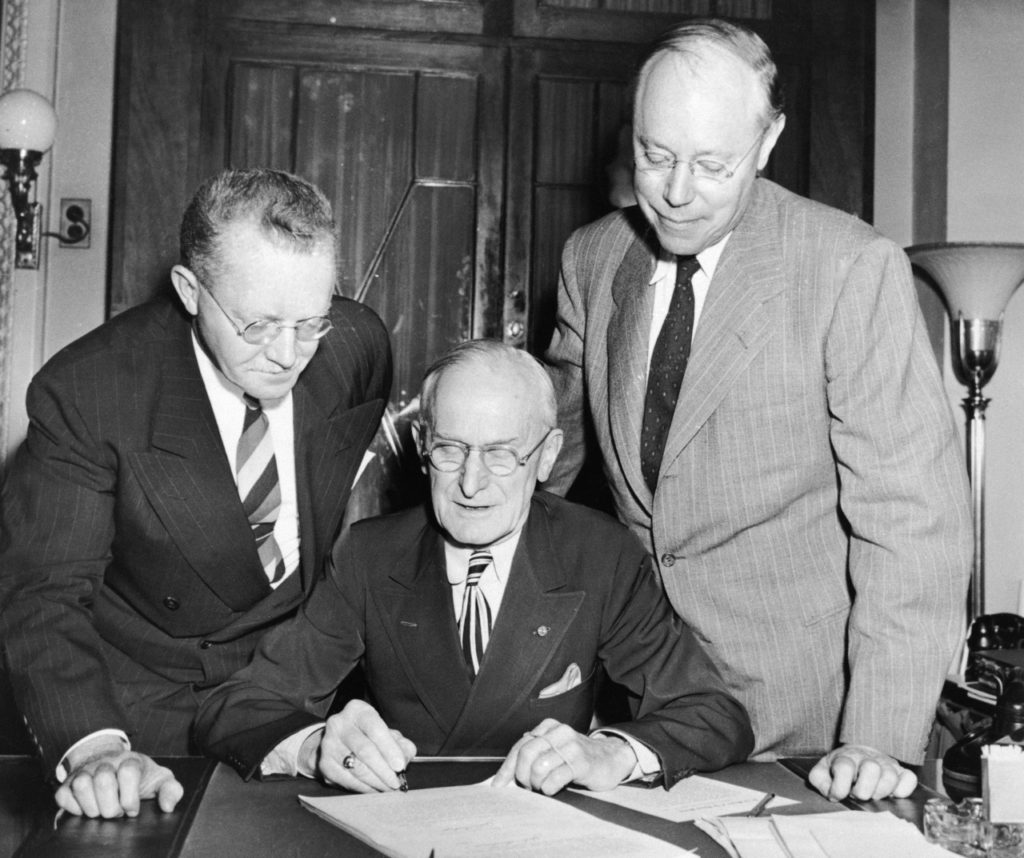 Carl Loeffler, center, Secretary of the Senate, certifies Senate passage over the presidential veto of the Taft-Hartley Labor Union Curbing Bill, June 23, 1947, Washington, D.C. Looking on are the bills co-authors, Rep. Fred Hartley, left, and Sen. Robert Taft. (AP Photo)