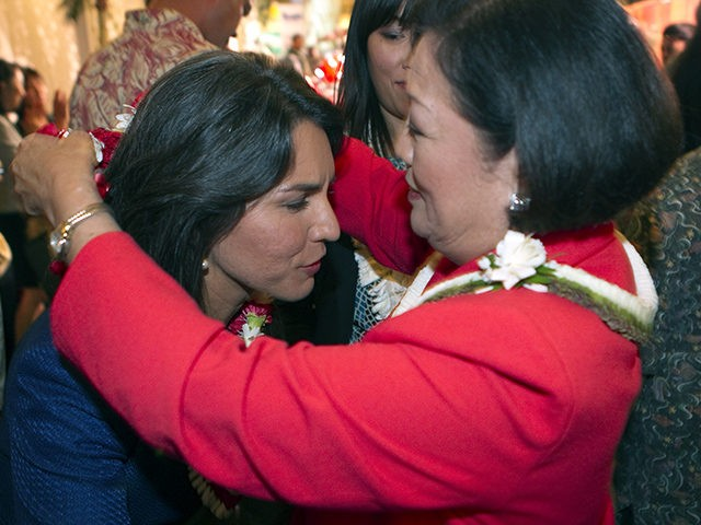 U.S. Rep. Mazie Hirono, right, places a flower lei on candidate Tulsi Gabbard at the Japanese Cultural Center, Tuesday, Nov. 6, 2012, in Honolulu. (AP Photo/Marco Garcia)