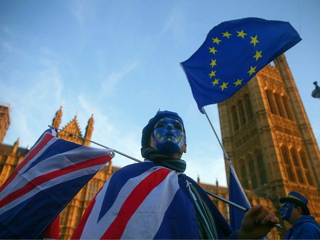 A pro-European Union, (EU), anti-Brexit demonstrator wears a mask featuring the EU flag as he holds Union and EU flags outside the Houses of Parliament in central London on December 18, 2017. (Photo by Daniel LEAL-OLIVAS / AFP) (Photo credit should read DANIEL LEAL-OLIVAS/AFP/Getty Images)