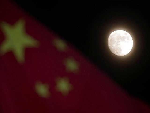 The moon is seen near a Chinese national flag in Beijing Sunday, Dec. 15, 2013. China's first moon rover touched the lunar surface and left deep traces on its loose soil, state media reported Sunday, several hours after the country successfully carried out the world's first soft landing of a …