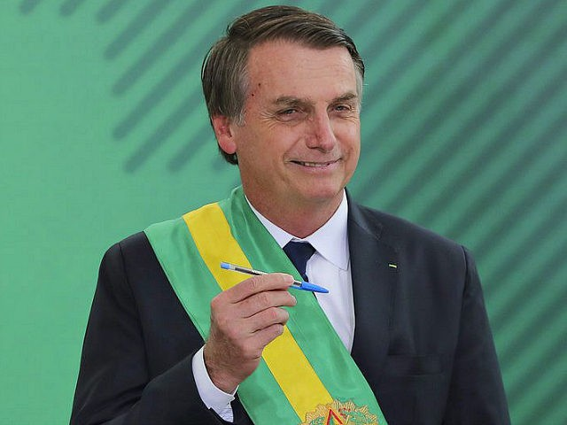 Brazil's new President Jair Bolsonaro poses with the pen used during the swearing-in ceremony for the minsters at the Planalto Palace in Brasilia on January 1, 2019, after his own inauguration at the national Congress. - Bolsonaro takes office with promises to radically change the path taken by Latin America's …