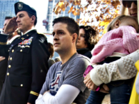 "In this Nov. 10, 2014, file photo, former U.S. Air Force Senior Airman Brian Kolfage, center, sits in a wheelchair next to his wife Ashley, right, who holds their daughter Paris, during the National September 11 Memorial and Museum's ""Salute to Service"" tribute honoring U.S. veterans in New York. Kolfage, …"