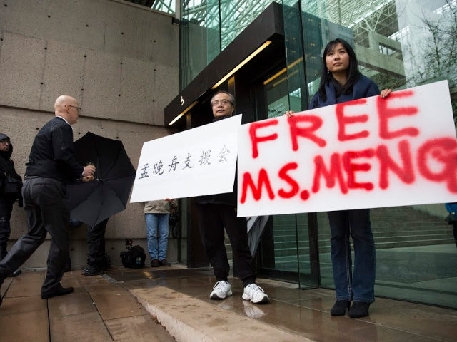 Robert Long (L) and Ada Yu hold signs in favor of Huawei Technologies Chief Financial Officer Meng Wanzhou outside her bail hearing at British Columbia Superior Courts following her December 1 arrest in Canada for extradition to the US, in Vancouver, British Columbia on December 11, 2018.