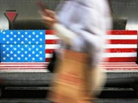 In this Sunday, Jan. 6, 2019, photo, a woman walks by a bench painted with the U.S. flag at the capital city's popular shopping mall in Beijing. A U.S. delegation led by deputy U.S. trade representative, Jeffrey D. Gerrish arrived in the Chinese capital for a trade talks with China. …