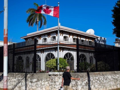 A man walks beside Canada's embassy in Havana, Cuba, Tuesday, April 17, 2018. Canada's foreign ministry said Monday that it is ordering families of diplomatic staff in Cuba to return home amid questions about mysterious health symptoms detected in 10 people who were stationed on the island.
