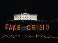 "Protesters hold up lights reading ""FAKE CRISIS"" behind lights arranged on the ground reading ""NO WALL"" outside the White House on Tuesday, January 8, 2019, as President Donald Trump delivers an address from the Oval Office on the federal government shutdown and border security."