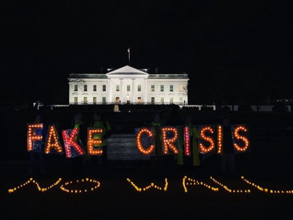"""Protesters hold up lights reading """"FAKE CRISIS"""" behind lights arranged on the ground reading """"NO WALL"""" outside the White House on Tuesday, January 8, 2019, as President Donald Trump delivers an address from the Oval Office on the federal government shutdown and border security."""