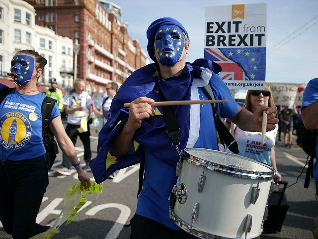Protesters march along the seafront wearing European flag masks in Brighton on September 24, 2017, on a march against Brexit. Britain's revitalised Labour opposition kicks off its annual conference today with leader Jeremy Corbyn set to lay out his party's agenda, free from the leadership challenges of previous years. / …