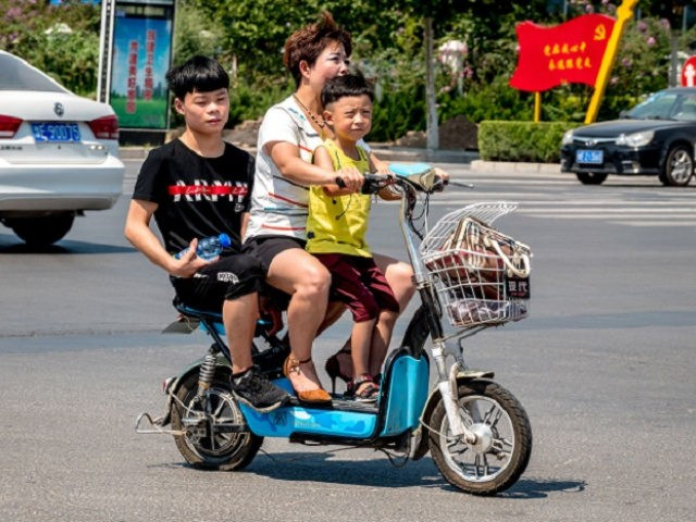A woman rides her scooter with two children in Huaxian county in China's central Henan province on August 28, 2018. - China's moves to combat an ageing population by relaxing decades-old curbs on family size have hit an unexpected snag: many parents are no longer interested in having more babies.