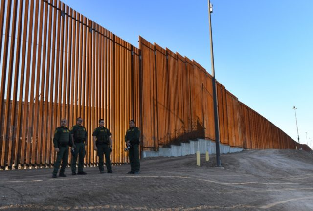 Border Patrol officers wait for US Department of Homeland Security Secretary Kirstjen M. Nielsen to inaugurate the first completed section of President Trumps 30-foot border wall in the El Centro Sector, at the US Mexico border in Calexico, California on October 26, 2018. (Photo by Mark RALSTON / AFP) (Photo …
