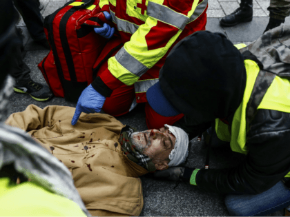 TOPSHOT - A firefighter helps an injured man near the Champs Elysees avenue in Paris on December 8, 2018 during a mobilisation against rising costs of living they blame on high taxes. - Paris was on high alert on December 8 with major security measures in place ahead of fresh …