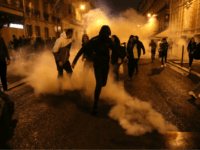 'Yellow vest' protestors (Gilets jaunes) and others run as police use tear gas to disperse them on a side street off the Champs-Elysees after New Year's celebrations in the French capital Paris on January 1, 2019. - A fireworks display and sound and light show under the theme 'fraternity' went …
