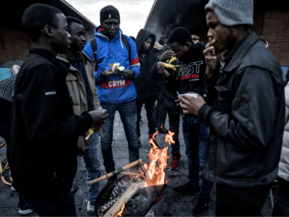 Asylum seekers from eastern African countries - mainly Sudan - warm themselves up around a brazier as they have a meal offered by volunteers of the 'Solidarite migrants Wilson' association, in Saint-Denis outside Paris where they live in a makeshift tent camp, on January 10, 2019. (Photo by Christophe ARCHAMBAULT …