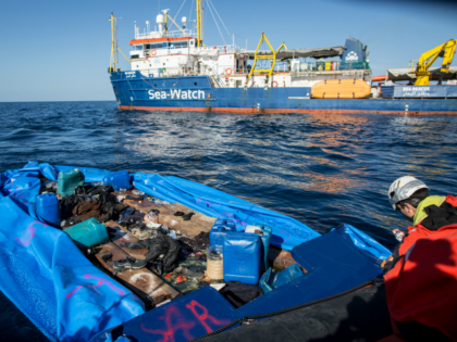 A Sea Watch 3 crew member marks with spray paint a rubber boat that the NGO destroyed after rescuing 47 migrants that were onboard, during a rescue operation by the Dutch-flagged vessel (Rear) off Libya's coasts on January 19, 2019. - The German charity group Sea Watch said on January …