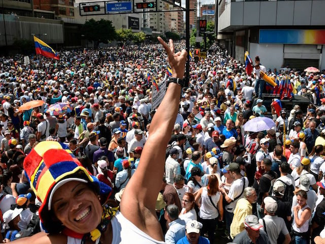 Venezuelan opposition supporters take to the streets to protest against the government of President Nicolas Maduro, on the anniversary of 1958 uprising that overthrew military dictatorship in Caracas on January 23, 2019. - At least four people died in overnight clashes in Venezuela as opposition supporters and regime loyalists prepared …