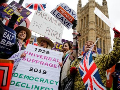 """TOPSHOT - Pro-Brexit activists hold placards and wave Union flags as they demonstrate outside of the Houses of Parliament in London on January 29, 2019. - British Prime Minister Theresa May will seek """"legal changes"""" to the Brexit deal she agreed with EU leaders only last month to try to …"""