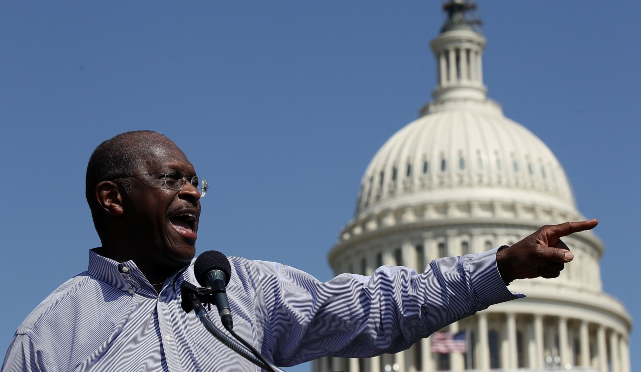 "WASHINGTON, DC - APRIL 16: Former Republican presidential candidate Herman Cain speaks at the ""Cain's Revolution on the Hill"" Tax Day Rally at the U.S. Capitol April 16, 2012 in Washington, DC. Cain spent the day promoting his 9-9-9 tax code plan in advance of tomorrow, the day that Americans …"