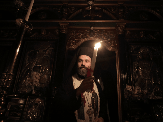 An Orthodox priest gives the Holy Fire to worshippers with a candle inside the Church of Metochi Panagiou Tafou in Athens, on April 15, 2017. The Holy Fire arrived from the church of the Holy Sepulcher in Jerusalem, earlier this evening. Greeks flock to churches around the country this week …