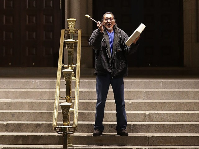 WASHINGTON, DC - APRIL 27: Native Youth Alliance Executive Director Nathan Phillips of Omaha Tribe in Nebraska beats a drum on the steps in front of the Trump International Hotel during a protest April 27, 2017 in Washington, DC. Organized by The Indigenous Environmental Network, the protesters gathered in front …