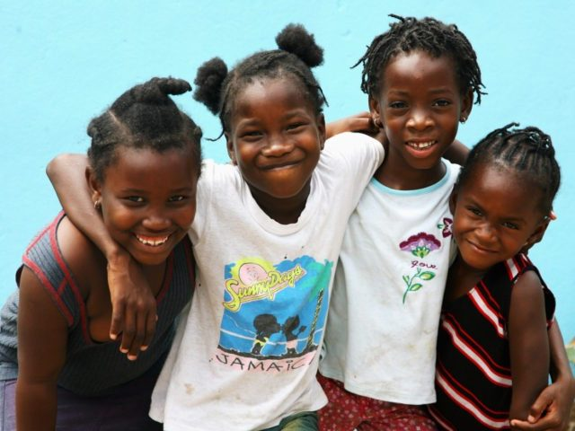KINGSTON, JAMAICA - MARCH 12: Young children pose for a photograph in Rose Town on March 12, 2008 in Kingston, Jamaica. Kingston is currently a city with one of the highest crime rates in the world. There are an average of four murders a day in a population of just …