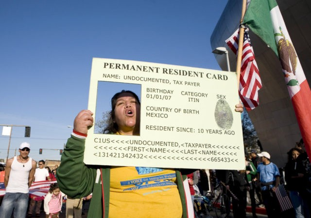Josephine Corral of Tacoma, Washington, puts her head through a large green card replica during a May Day march May 1, 2008 in Seattle, Washington. The four-mile march drew thousands of people and clogged traffic in downtown Seattle during rush hour. (Photo by Stephen Brashear/Getty Images)