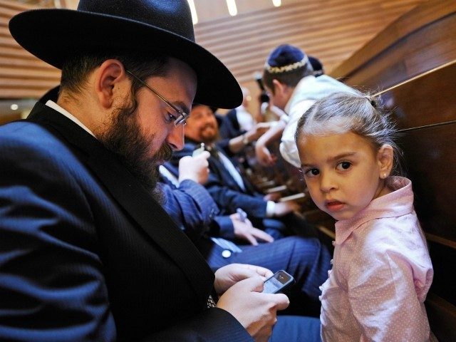 BERLIN, GERMANY - JUNE 19: A young girl looks on as her father checks his iPhone prior to an ordination ceremony for six rabbinical students at Gedola Yeshiva at the Chabad Education Center on June 19, 2011 in Berlin, Germany. Rabbinical centers across Germany are generating a new generation of …