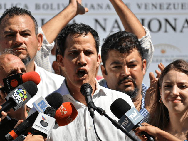 Venezuela's National Assembly president Juan Guaido, accompanied by his wife Fabiana Rosales gestures before a crowd of opposition supporters during an open meeting in Caraballeda, Vargas State, Venezuela, on January 13, 2019. - The president of the opposition-controlled but sidelined National Assembly was released less than an hour after being …