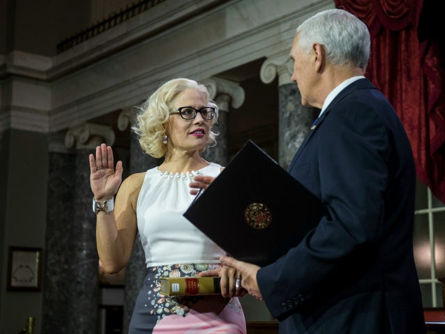 Senator Kyrsten Sinema (D-AZ) participates in a mock swearing in ceremony with Vice President Mike Pence on Capitol Hill on January 3, 2019 in Washington, DC. (Photo by Zach Gibson/Getty Images)
