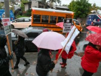 A school bus arrives with students as teachers and their supporters picket outside John Marshall High School in Los Angeles, California on the first day of the teachers' strike, on January 14, 2019. - Teachers of the Los Angeles Unified School District (LAUSD), the second largest public school district in …