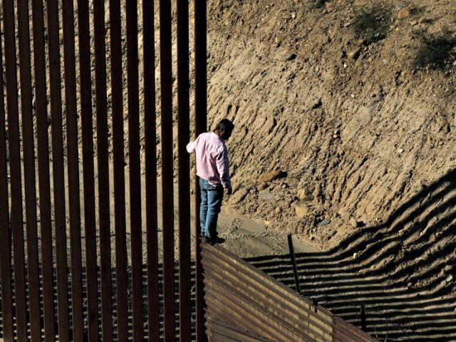 A migrant near the border fence between Tijuana, Mexico, and San Diego. President Trump has said there is a national security crisis at the border.