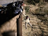 A migrant jumps the border fence to get into the U.S. side to San Diego, Calif., from Tijuana, Mexico, Tuesday, Jan. 1, 2019. Discouraged by the long wait to apply for asylum through official ports of entry, many migrants from recent caravans are choosing to cross the U.S. border wall …