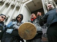 Native American protestors hold hands with parishioner Nathanial Hall, right, during a group prayer outside the Catholic Diocese of Covington Tuesday, Jan. 22, 2019, in Covington, Ky. The diocese in Kentucky has apologized after videos emerged showing students from Covington Catholic High School mocking Native Americans outside the Lincoln Memorial …
