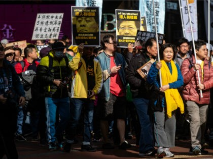 Protesters display placards of former chief executive Leung Chun-ying (centre L) and current leader Carrie Lam (centre R) during the annual New Year's Day pro-democracy rally in Hong Kong on January 1, 2019. - Hong Kong's embattled democracy advocates kicked off 2019 with a large street rally on January 1, …