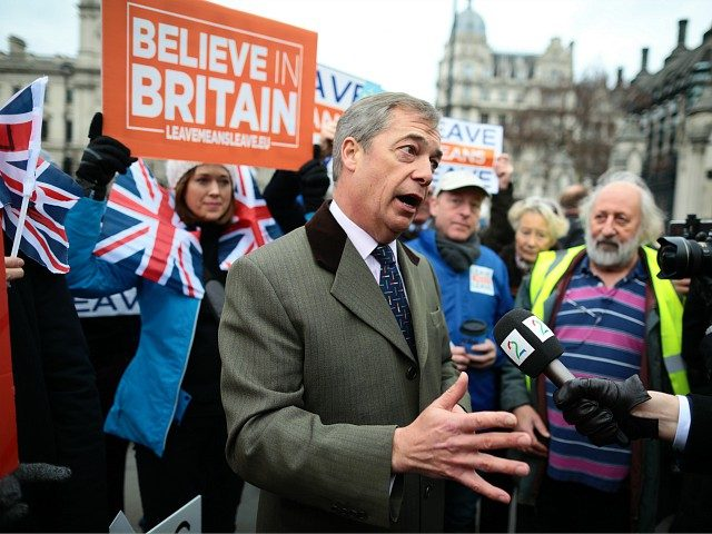 LONDON, ENGLAND - JANUARY 15: Crowds hold pro-Brexit signs and Union Jack flags near former UKIP Leader Nigel Farage speaking to the media in Parliament Square outside the Palace of Westminster on January 15, 2019 in London, England. MPs vote on Theresa May's Brexit deal as it finally reaches the …